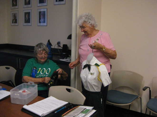Virginia Walton (left) and Bonnie Johnson checked to make sure the badge sash was correct.