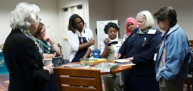 Committee member Julie Lineberry (second from right) identifies an old Girl Scout publication.