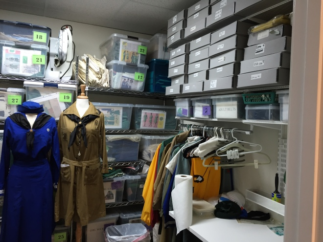 The uniform room is compact, but includes storage, a desk, and an iron and ironing board behind the door.