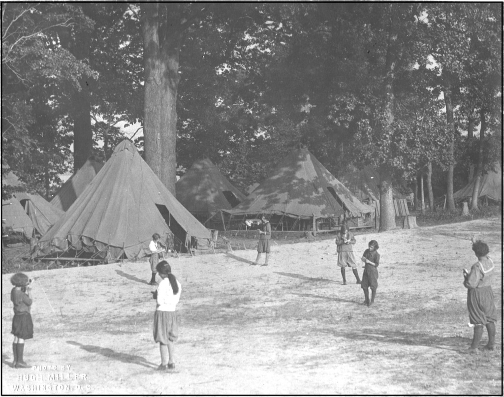 Vintage Girl Scouts using compasses outside teepee tents.